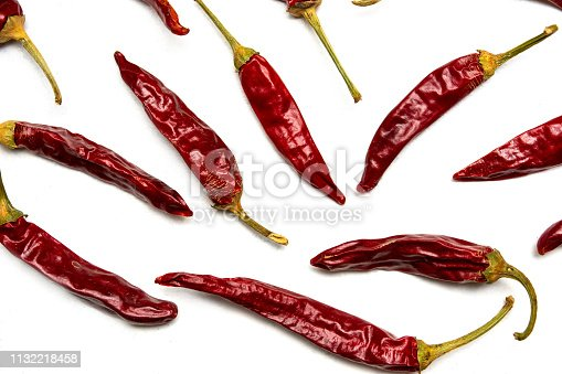 Dried red peppers on white background flat lay