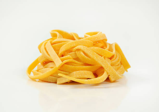 dried ribbon pasta bundle of dried ribbon pasta on white background tagliatelle stock pictures, royalty-free photos & images