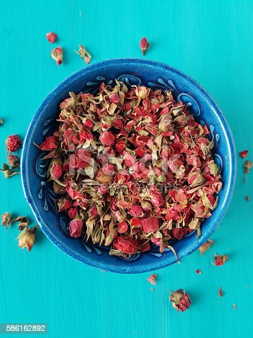 dried rose buds on a turquoise background