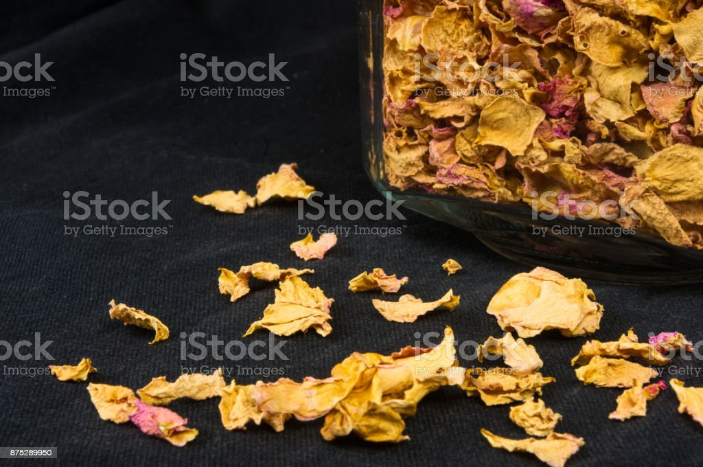 dried rose petals in a glass jar with lid on a black background