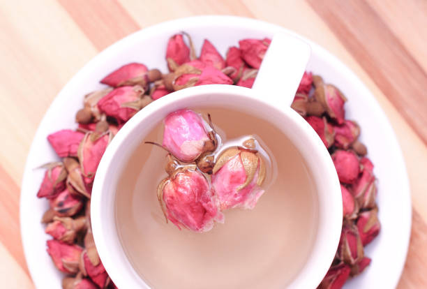 dried roses and a cup of tea - rosen tee stock-fotos und bilder