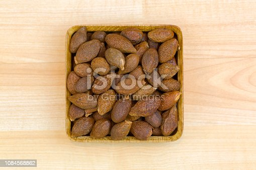 Dried seeds of Malva nut (Taiwan sweet gum) used in traditional Chinese medicine, top view on wooden background (Scaphium affine)