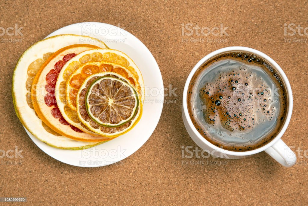 Dried slices of various citrus fruits and black coffee in a white Cup stock photo