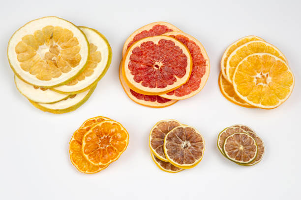 Dried slices of various citrus fruits on white background stock photo