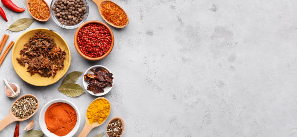 dried spices and seasonings in bowls on grey background - spezia foto e immagini stock
