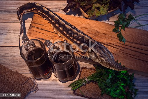 dried sturgeon with dark beer and greens on a wooden background