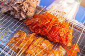Dried sweet stingray orange color roast on a wooden stick for sale grill eat at street food in Thailand.