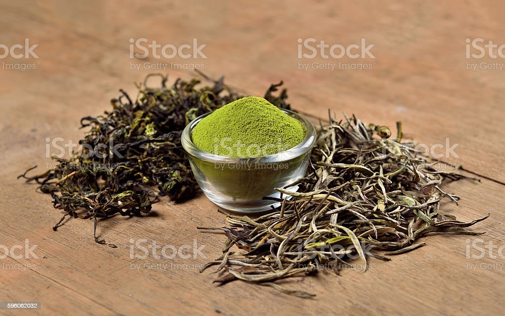 Dried tea leaf and powder on wooden background royalty-free stock photo
