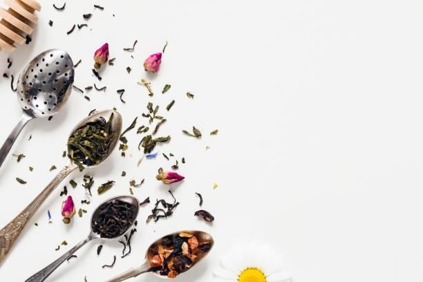 getrocknete teeblätter in teelöffel auf weißem hintergrund - grüner tee koffein stock-fotos und bilder