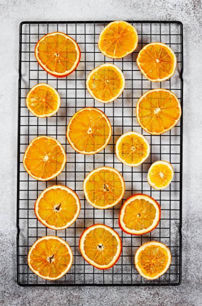 getrocknete dünne, durchscheinende orangenscheiben auf dem teiggestell - orangenscheiben trocknen stock-fotos und bilder