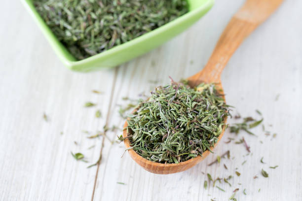 dried thyme on wooden surface stock photo