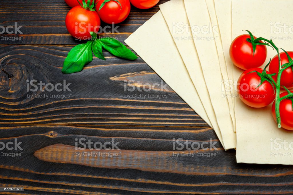 dried uncooked lasagna pasta sheets and tomato royalty-free stock photo