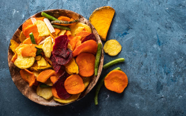 Cтоковое фото Dried vegetables chips from carrot, beet, parsnip and other vegetables on blue backgrounds. Organic diet and vegan food