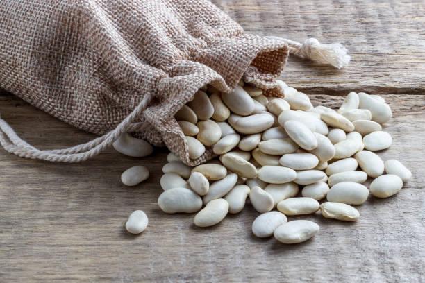 dried white beans in a bag on a wooden background - fagioli cannellini foto e immagini stock