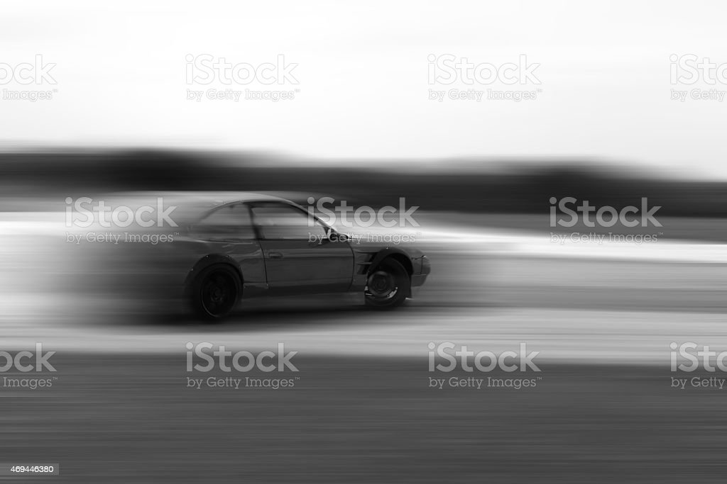 drift car motion blur on hard black and white stock photo