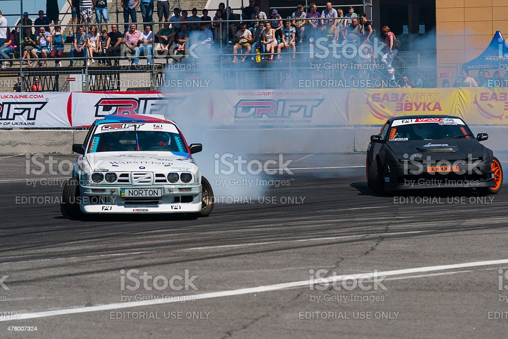 Unknown riders on the car brand Nissan and BMW overcomes the track in...