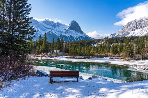 Natural scenery in early winter season sunny day morning. Drift ice floating on Bow River. Clear blue sky, snow capped Mount Lawrence Grassi in background. Landscape in Town Canmore, Alberta, Canada.