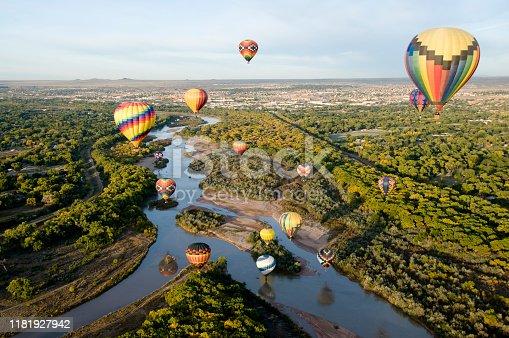 Hot air balloons drifting over the Rio Grande river in Albuquerque, New Mexico.