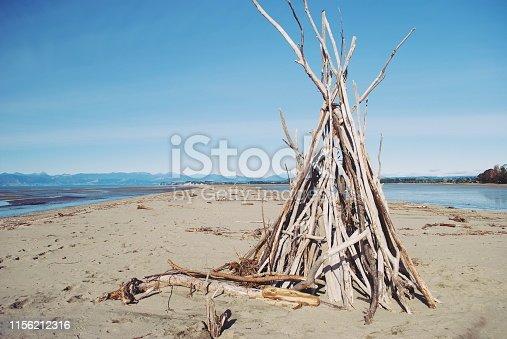 A Driftwood Beach Hut on a Coastal Sand Bar in Estuary.