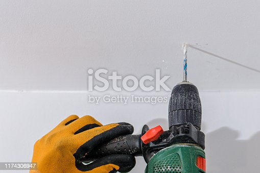 Man with orange gloves using an electric drill on a wall