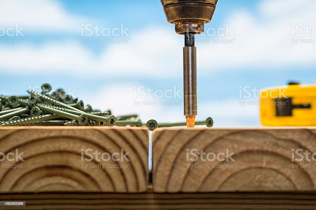 Drill driving screws into a pressure treated deck stock photo