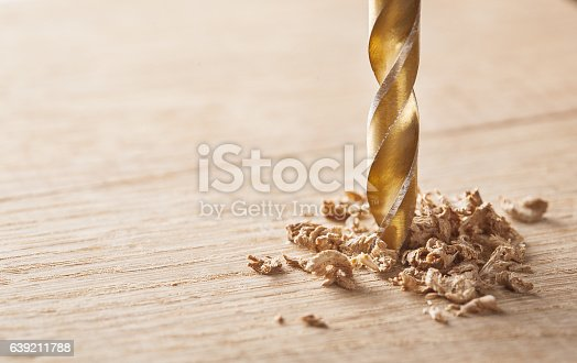 drill makes a hole in the wooden oak table wood