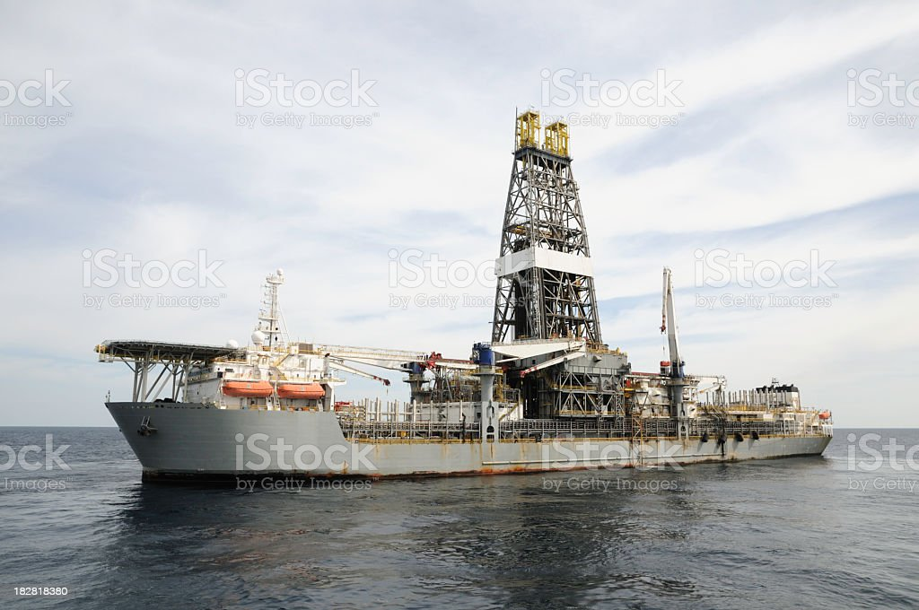 A drill ship at open ocean drilling location. Ship has helideck at...