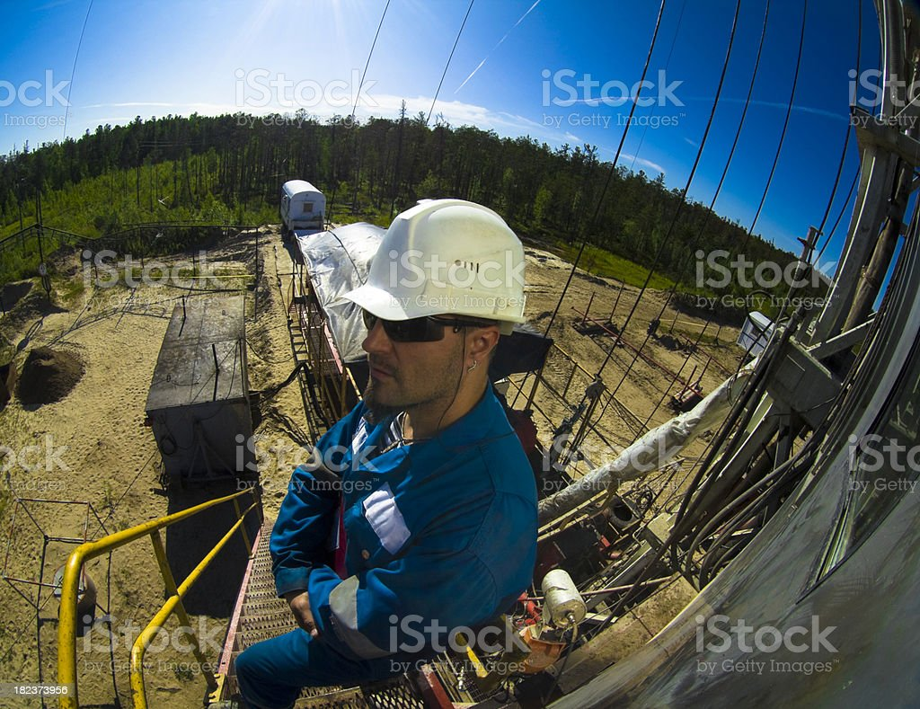 Driller standing on the ladder stock photo