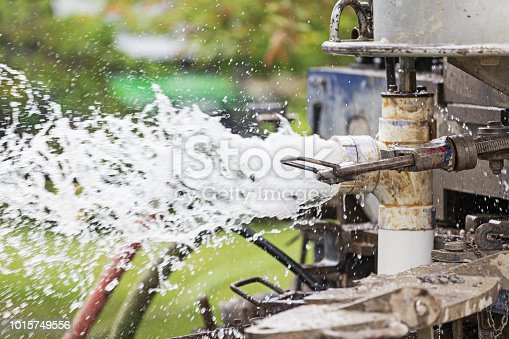 Close-up image of the process and equipment of drilling a new residential water well.  This image shows water forcefully spraying out of the new pcv water pipe.