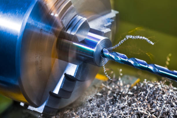 Drilling detail. Axial hole. Lathe working. Workpiece turning. Twisted metal swarf pile. Machining stock photo