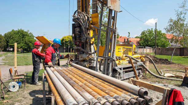 Drilling Geothermal Well Drilling geothermal well for a residential geothermal heat pump. Workers on Drilling Rig.  drill stock pictures, royalty-free photos & images