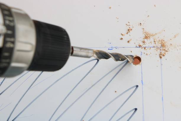Drilling hole in a white wooden board stock photo