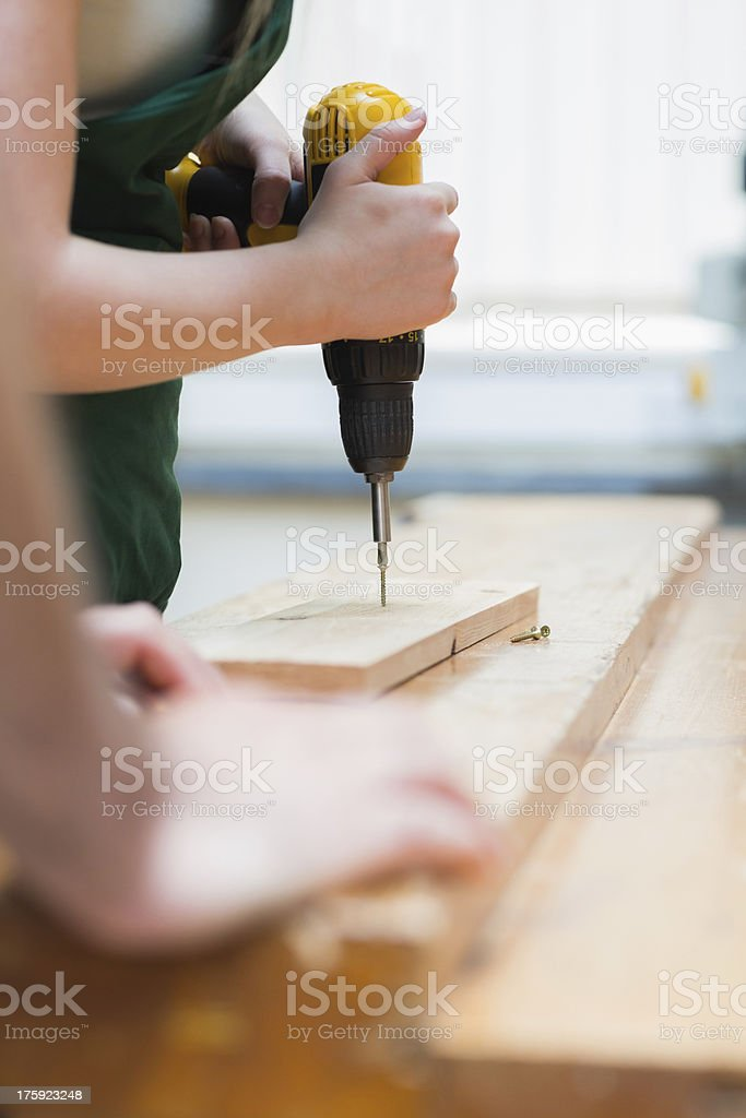Drilling hole in a wooden board on the workbench royalty-free stock photo