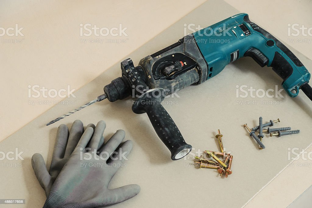 Drilling machine, dowels and gloves stock photo