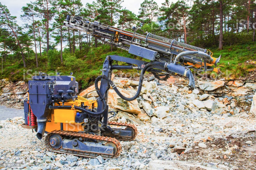 Drilling machine for demolition in a rock quarry stock photo