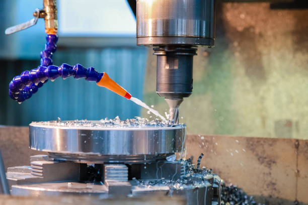 Drilling machine makes a hole in the metal product. Coolant is pouring on the drill. Drilling machine makes a hole in the metal product. Coolant is pouring on the drill. metal worker stock pictures, royalty-free photos & images