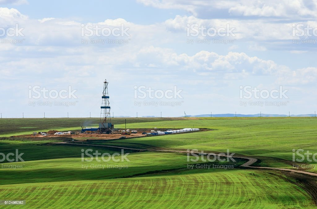 Drilling rig among agricultural fields. View from above stock photo