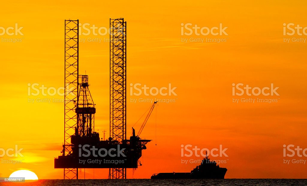 Drilling rig and supply vessel stock photo