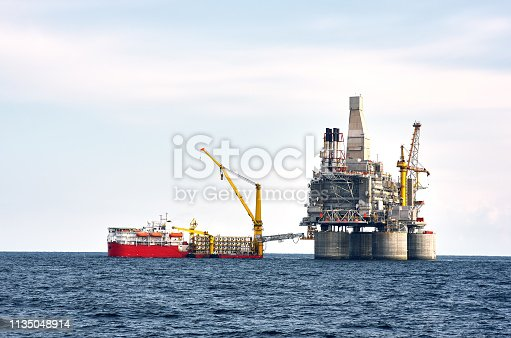 Drilling rig and support vessel on offshore area, sea and clean blue sky