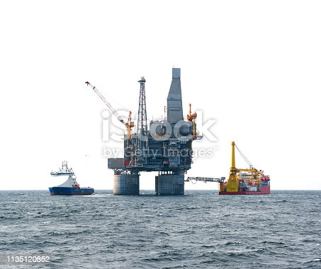 Drilling rig and support vessel on offshore area, sea and white sky background