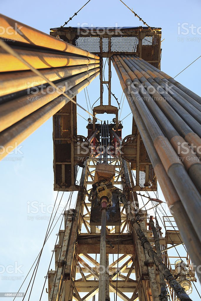 Drilling rig at sunset with ligth on pipes stock photo