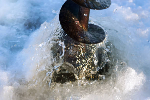 drilling through the ice ice fishing - drill stock photos and pictures