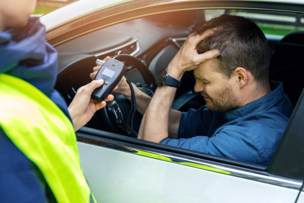 drink and drive concept - sad drunk man sitting in the car after police alcohol test with alcometer stock photo