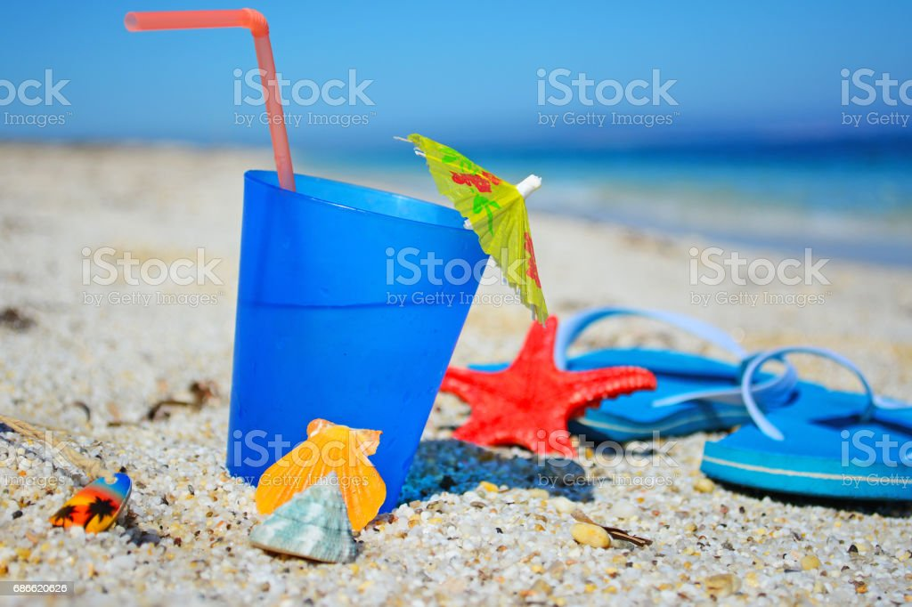 drink and flip flops on the sand royalty-free stock photo