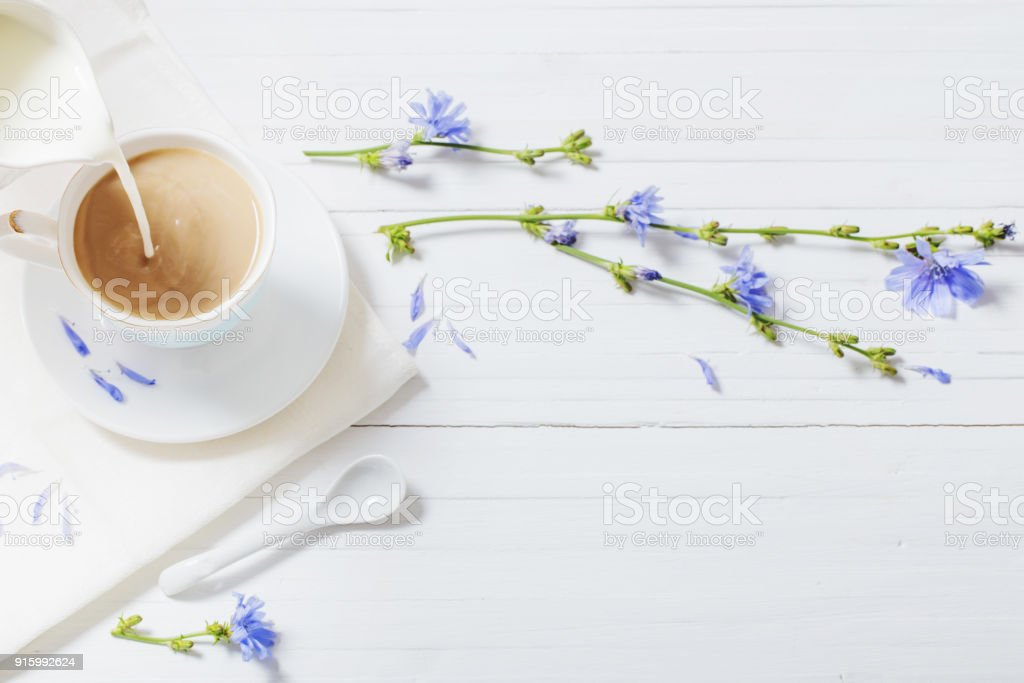 Drink from chicory in a cup on the white wooden table stock photo