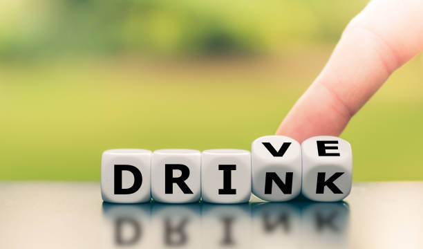 """Drink or drive? Hand turns dice and changes the word """"drink"""" to """"drive"""", or vice versa. stock photo"""