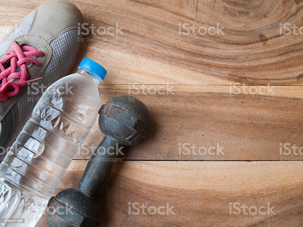Drink water bottle ,metal dumbbell and on a old wooden background,for...