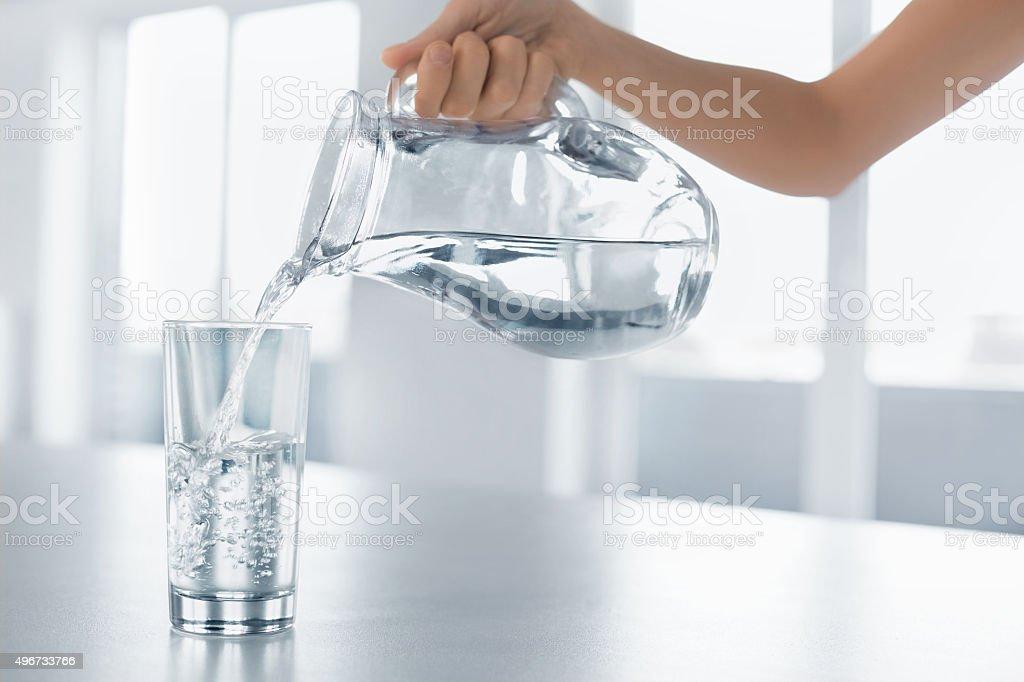 Beba agua. Mujer de la mano vertiendo agua en vidrio del Pitcher - foto de stock