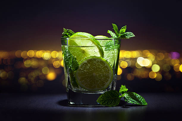 Drink with lime and peppermint leaves Drink with lime , ice  and peppermint leaves on a background of night city mojito stock pictures, royalty-free photos & images