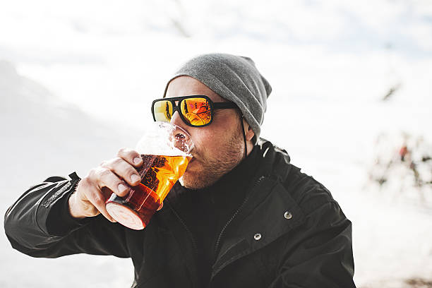 Beber una cerveza en después de esquiar - foto de stock